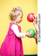 Little child girl playing with ball in kindergarten in...