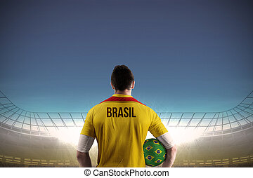 Composite image of brasil football player holding ball -...
