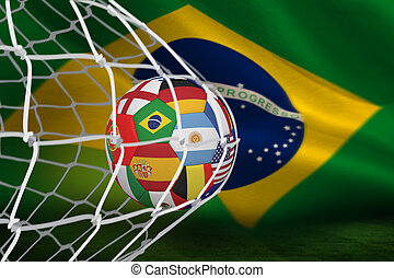 Football in multi national colours at back of net against...