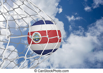 Football in costa rica colours at back of net against bright blue sky with clouds