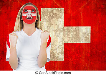 Composite image of excited fan in swiss face paint cheering