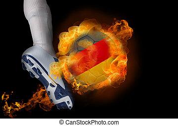Football player kicking flaming germany ball against black