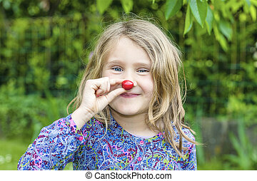 Child with cherry in the hand in a garden