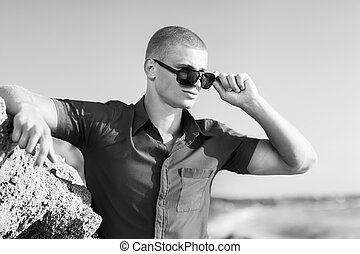 fashion man on the beach in sunglasses