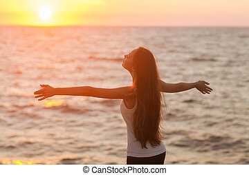 Free woman enjoying freedom feeling happy at beach at...