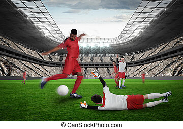 Football player in red kicking against vast football stadium...