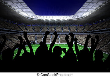 Silhouettes of football supporters against large football...