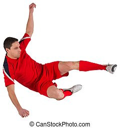 Fit football player jumping and kicking on white background