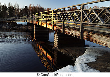 old wooden bridge over the river at sunset