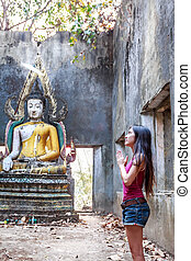Asian Girl Greets in old temple traditional way with both...