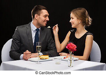 smiling couple eating dessert at restaurant - restaurant,...
