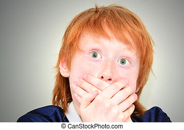 Scared red haired boy closing mouth with hands