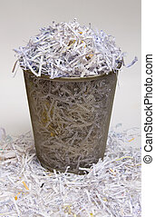Shredded Paper - A waste basket overflowing with shredded...