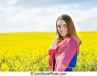Girl in colza field - Happy young girl in blue dress and red...