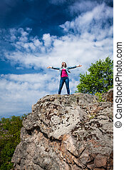 Outdoor photo of beautiful woman standing on top of high...