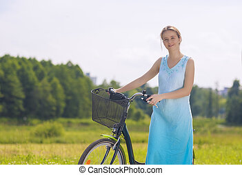 Young and Beautiful Caucasian Blond Having a Stroll in the Park Area With Her Bicycle. Horizontal Image Composition