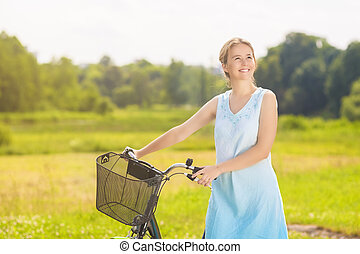 Happy Beautiful Caucasian Blond Having a Stroll in the Park Area With Her Bicycle. Horizontal Image Composition