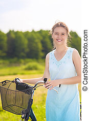 Portrait of Young Happy Caucasian Blond With Bicycle in the Park on a Sunny Day. Vertical Image