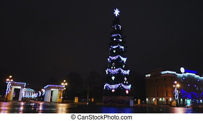 Cars passing by Smolensky Cathedral and Christmas tree decorated with colorful lights