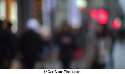Evening city street with pedestrians and blurred lights -...