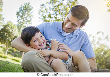 Loving Father Tickling Son in the Park