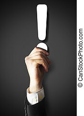 businessman holding white exclamation point in hand