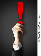 businessman holding red exclamation point in hand