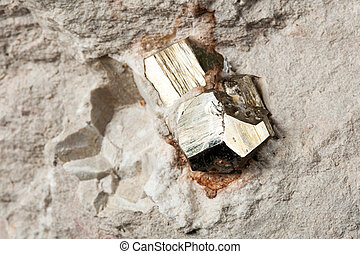 Cubic pyrite growing on the rock wall