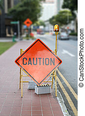 Caution road street sign with defocused street in background
