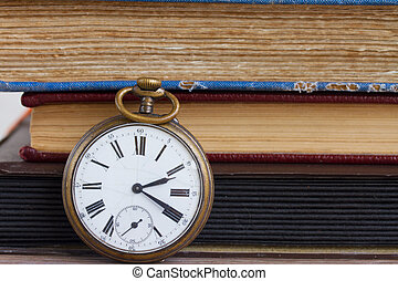 antique clock on books background