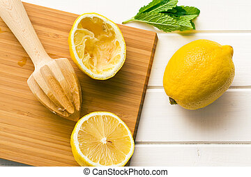 squeezed lemon fruit and citrus reamer on kitchen table
