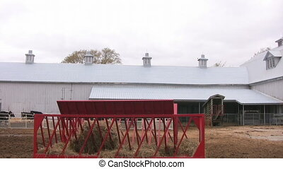 Pan of large cattle barn - Pan of a large gray cattle barn...