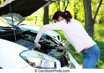 Beautiful woman checking her car engine