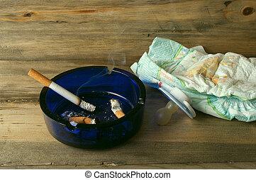 ashtray, cigarette, baby diaper and nipple