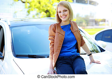 Young happy girl sitting on the hood of a car