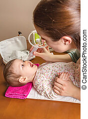 Mother cleaning mucus of baby with nasal aspirator - Mother...