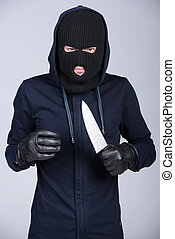 Criminality - Masked man aims with knife. on gray background