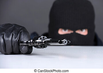 Criminality - Masked robber with gun aiming into the camera...