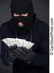 Criminality - Criminal in a balaclava holding a fistful of...