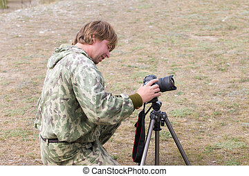 keen photographer with camera and tripod in nature