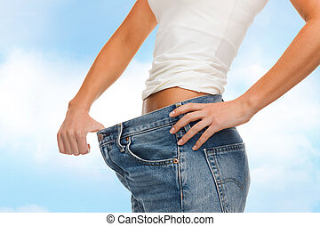 close up of female showing big jeans - healthcare, diet and...