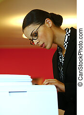 using Xerox - Pretty young businesswoman using Xerox machine...