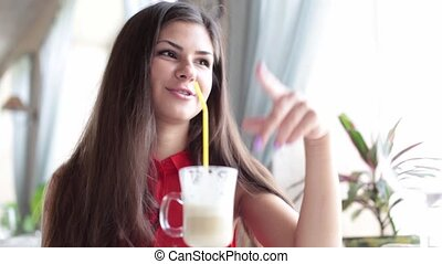 Young woman is speaking to somebody in a cafe and drinking...