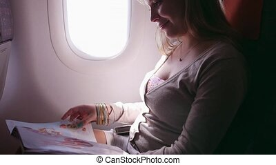 Happy woman traveling on airplane - People and travel, young...