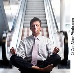 No more rush! - Businessman meditating in lotus position in...