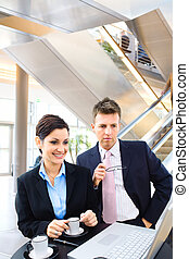 Business people in lobby - Business people working over a...