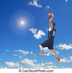 basketball player in the sun - basketball player dunking in...