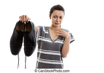 out the door with them - woman holding a pair of men smelly...