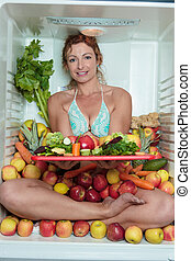 Woman sitting in a fridge in the lotus position surrounded by fruits holding a cutting board with cut apples