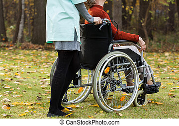 Disabled and nurse on a walk in park